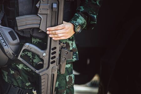Infantry army soldier hand holding machine gun for security guard standing with space for text.