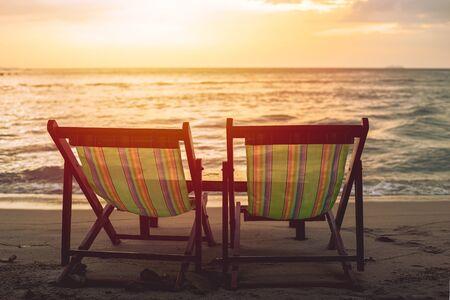 Dos sillas de cama de playa en blanco en la playa con fondo de cielo crepuscular de sol.