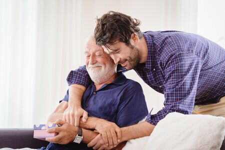 young man hugs the uncle old man warmly inside the house, son happy and love his father or grand father with gift box concept Banque d'images