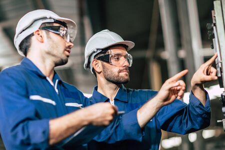 engineer teamwork checking control panel and teaching new worker to operating control the machine in factory. Stockfoto