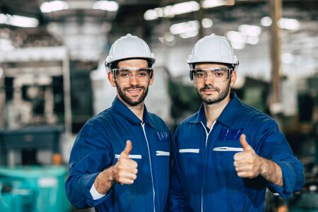 Une équipe de travailleurs heureuse souriante montre le pouce vers le haut pour un bon travail en usine. Banque d'images