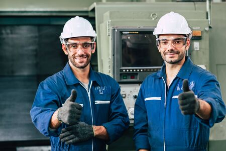 Happy worker team smiling hand show thumb up for good working in factory.