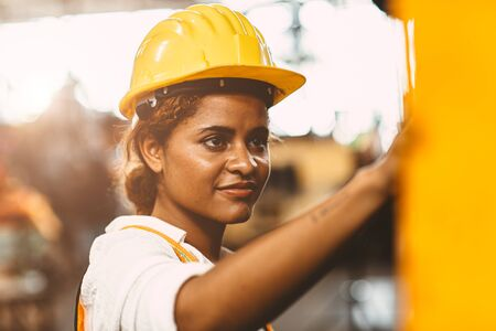 happy African American woman worker with safety suit helmet enjoy smiling working as labor in heavy industry factory with steel machine operator for good welfare. Archivio Fotografico