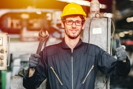 Portrait of young American happy worker enjoy happy smiling to work in a heavy industrial factory.Thumb up with big wrench.