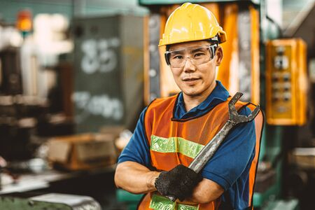 Portrait of Asian Thai Chinese labor happy worker enjoy happy smiling to work in a heavy industrial factory to fix machine with big wrench. Imagens