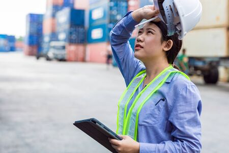 woman worker tired fatigue from hardwork overload and outdoor hot weather sweating in port cargo shipping industry.
