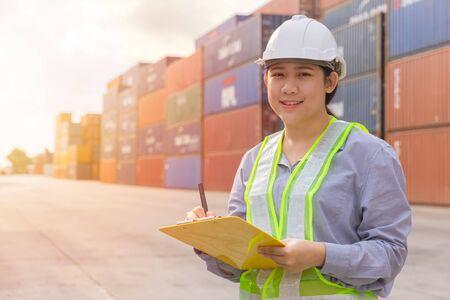 Asiatische junge Teenager glückliche Arbeiter, die Lagerbestände im Versandhafen überprüfen, verwalten Import-Export-Frachtcontainer.
