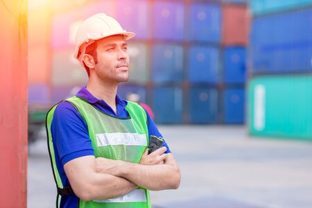 portrait of shipping worker man proud of work in cargo port for import export goods standing smile. Standard-Bild