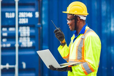Black African happy worker working in logistic communication using radio and laptop to control loading containers at port cargo to trucks for export and import goods.