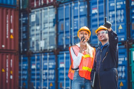 logistic worker man and woman working team with radio control loading containers at port cargo to trucks for export and import goods. Standard-Bild