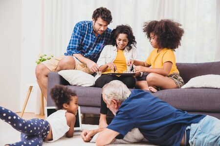 Lovely home family stay together in living room father mother and grandfather playing with daughter mix race.
