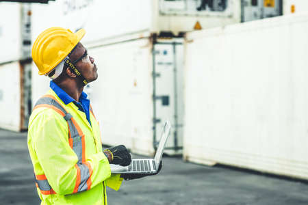 Black African worker working in logistic shipping using laptop to control loading containers at port cargo for import export goods foreman looking high for future
