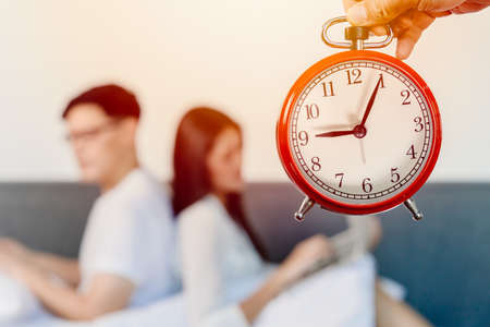 Alarm clock with blur people sitting facing back for bad relationship times of living together family hours or couple lover boring each other concept.