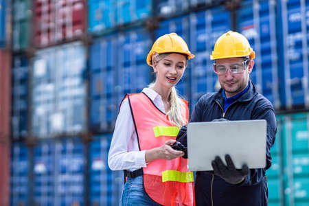 Logistic worker man and woman working team with online wireless laptop control loading containers at port cargo to trucks for export and import goods