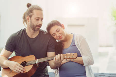 Husband with pregnant wife stay home lovely playing guitar music for baby kissing and showing love together