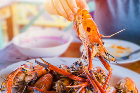 Asian Thai people eating grilled giant river prawn shrimp bbq with spicy sweet and sour seafood dipping sauce yummy popular food in Thailand.