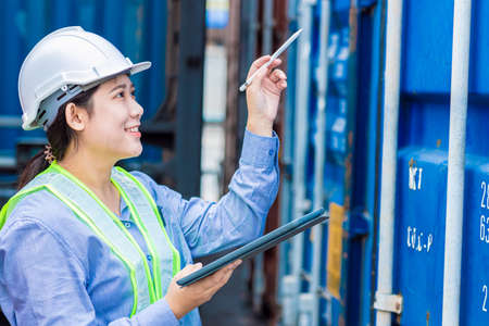 Asian young teen working in shipping logistic cargo load area use tablet wireless technology to checking customs detail of import export container code.