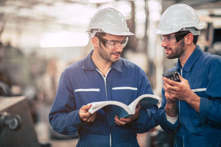 Engineer team talking together teach and learn engineering technical about using machine with open instruction manual text book in factory workplace.