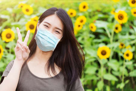 Cute girl teen happy ware face mask for protect Coronavirus or Air pollution or flower pollen allergy on sunflower park background