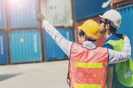 Staff foreman at warehouse container cargo loading area good cooperate join working team together hand pointing forward
