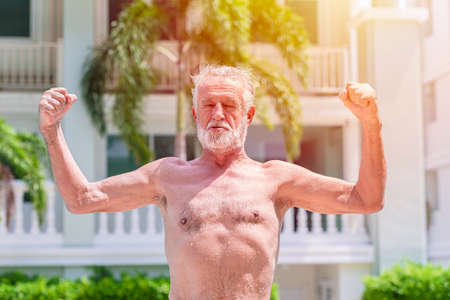 Strong healthy elder man show muscle and fit expression outdoor