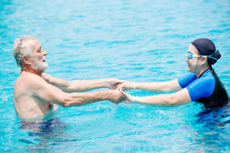 Healthy couple elder wife and husband enjoy playing together in swimming pool Zdjęcie Seryjne