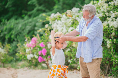 Grandpa dressed up hat to grandchildren little girl during holiday trip at park flower field looks cute lovely and warm 免版税图像