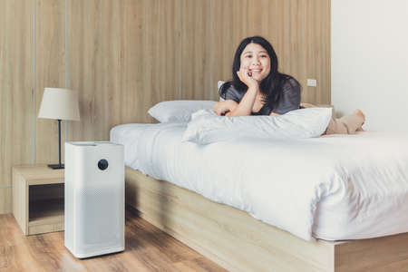 Woman at home bedroom happy enjoy with air purifier for clean PM 2.5 dust pollution and stay healthy