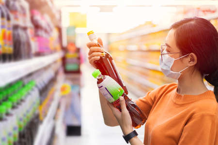 Asian Customer shopping in supermarket with face mask choice select and compare fish sauce by reading products detail label on shelf