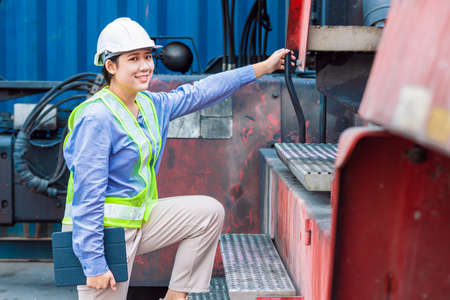 Asian young teen happy smile engineer worker working with heavy industry machine with safety suit and hardhat, looking camera.
