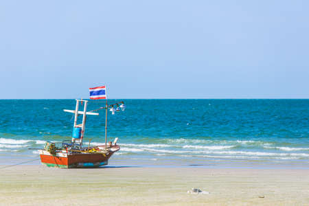 A stranded boat with Thai flag on the beach