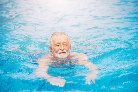 Caucasian healthy elder swimming at the swimming pool for relax in summer holiday activity