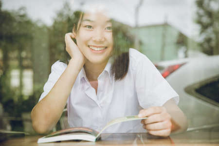 Asian university girl teen cute smiling looking through glass window shadow reflect effect while sitting reading book