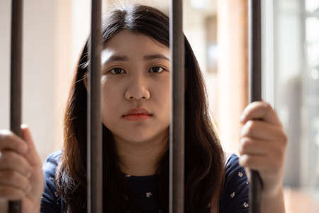 no freedom girl teen in jail hand at cage looking camera