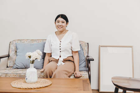 Plump and healthy housewife sitting in the home living room warm smiling, looking at the camera