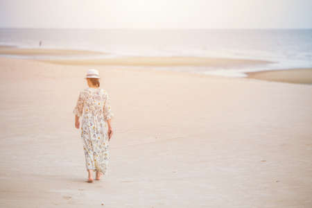 woman walking on the beach alone lonely with space for text Zdjęcie Seryjne