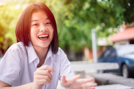 Happy smile Asian student girl teen young cute sitting outdoor looking camera with copy space Zdjęcie Seryjne