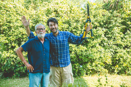 Happy gardener, elder with man enjoy pruning bushes at backyard for stay home activity in holiday looking camera