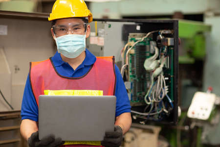 Asian Worker wear disposable face mask for protection Corona Virus Spreading and Smoke dust air pollution filter in factory for healthy labor care. 免版税图像