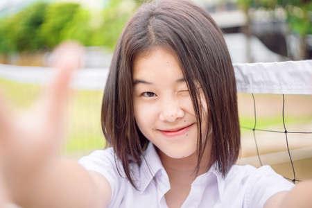 Cute asian student girl winking eye smiling expression selfie camera, close-up shot