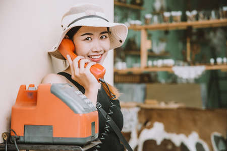 Asian girl teen cute hipster style fashion portrait holiday summer travel  dressing vintage color film tone, using telephone calling concept