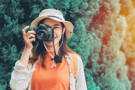 Pritty young Asian photographer girl teen travel with camera trip take a photo tourist lifestyle standing smile with hat