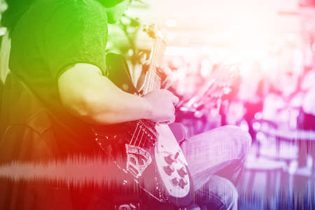 musician guitarist with overlay colorful effect for music entertainment event on stage show background.