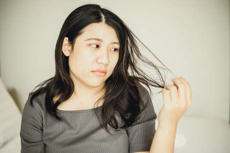 Asian women bore and moody with damaged hair and split ends due to lack of nourishment.