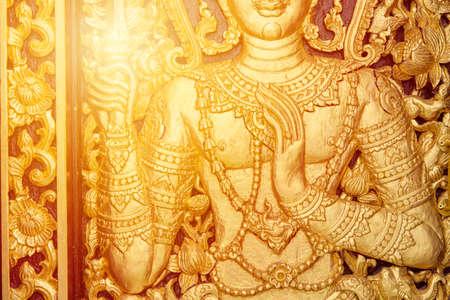 Thai woodcraft golden art god pattern at temple door Buddhist religion culture pattern for background