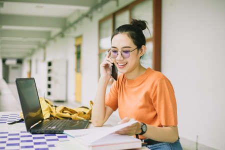 University girl teen using phone call talking with friend while working in campus Zdjęcie Seryjne