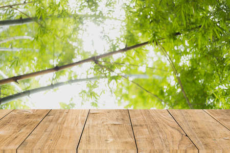 blur bamboo forest green tree with wooden table top for products montage advertising background 免版税图像