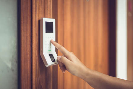 hand typing password at electronic door lock and security system panel.