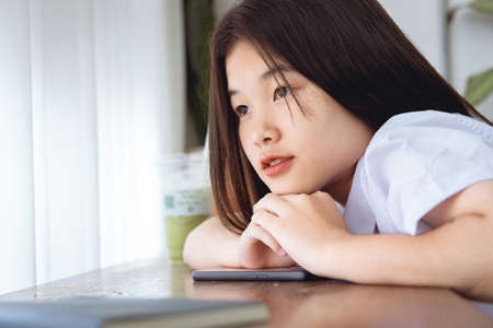 Cute Asian university students looking windows lovely teen missing or waiting someone love emotion