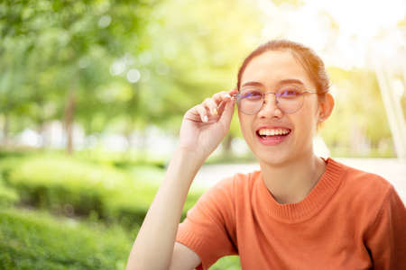 Asian woman wearing glasses happy smile with green nature outdoor background Zdjęcie Seryjne